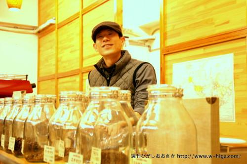 コーヒー豆を入れたビンを前に熱く語る井本さん