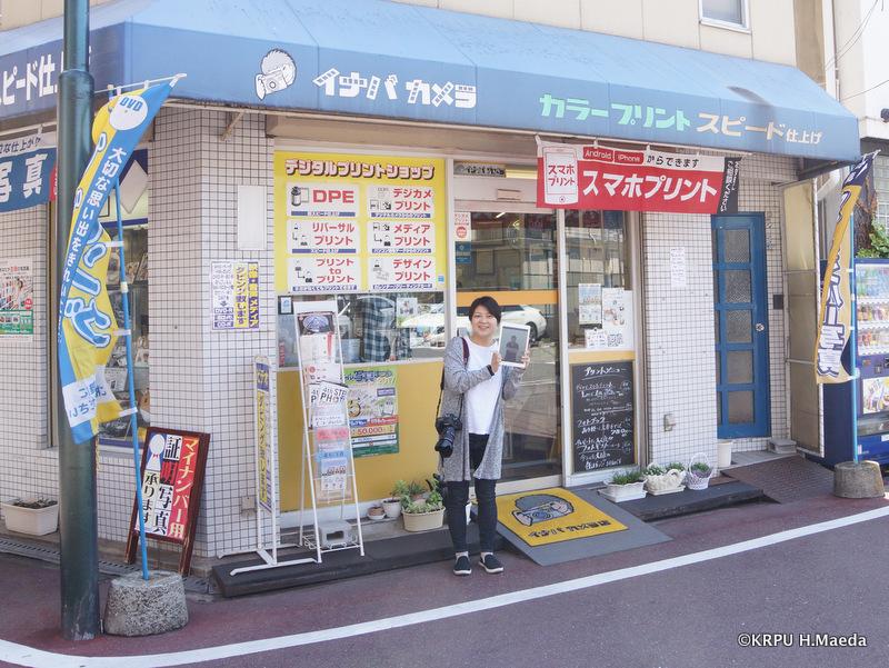 お店の前で、私の写真を見せて笑ってくれる仁美さん。